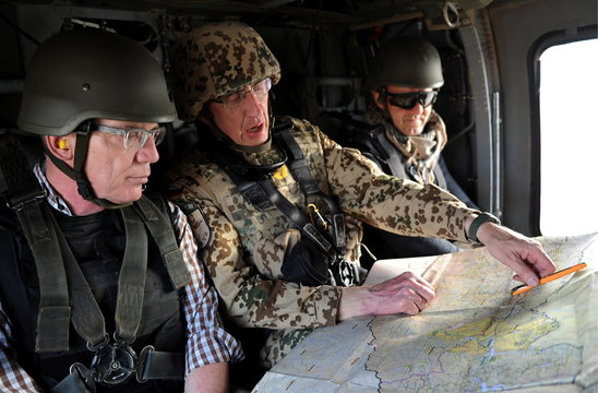 German Defence Minister de Maiziere and commander of the ISAF forces in the Northern Afghanistan look at map during visit a Bundeswehr camp near Hazrat-e Sultan
