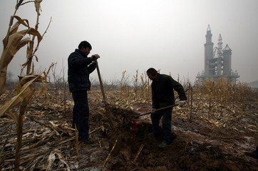Farmers dig a water well in a field that includes an abandoned building that was to be part of an amusement park called 'Wonderland', on the outskirts of Beijing