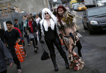 Nicci Fette, dressed as comic book character Red Sonja, and Courtney Rose, dressed as Red Cat, pose for a photograph at New York's Comic-Con convention