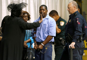 An inmate with the Louisiana Department of Corrections is consoled by friends and family they attend the funeral of Alton Sterling, in Baton Rouge