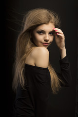 Tender young blonde model with long lush hair at studio