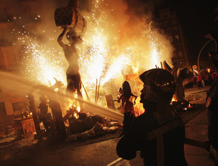 A firefighter sprays water as effigies burn during finale of the Fallas festival, which welcomes spring and honours Saint Joseph's Day, in Valencia