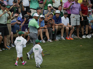 U.S. golfer Tiger Woods walks with his children Sam and Charlie as they caddie for him during the par 3 event held ahead of the 2015 Masters at Augusta National Golf Course in Augusta