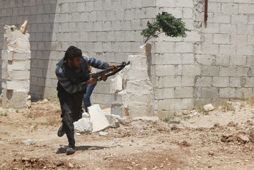 A Free Syrian Army fighter fires his weapon during clashes with forces loyal to Syria's President Bashar al-Assad in Sheikh Najjar in Aleppo