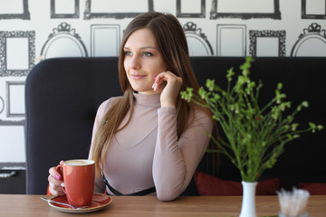 girl in a cafeteria with a mug of tea or coffee