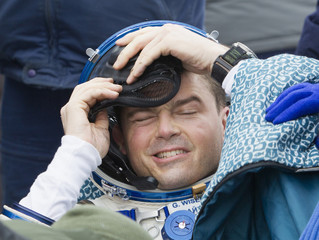 International Space Station crew member Wiseman of the U.S. takes off his helmet after landing in a remote area near the town of Arkalyk in northern Kazakhstan