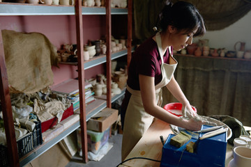 Young woman working at pottery wheel