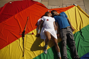 Activists Mario Almeida and Jose Criado kiss as they lie on a heart-shaped cloth with rainbow colours during a protest in Malaga, southern Spain