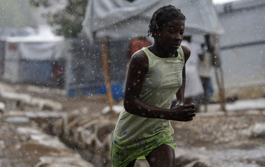 A girl runs under the rain at Petion Ville Club golf course IDP camp in Port-au-Prince