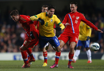 Hernanes of Brazil is tripped by Bystrov of Russia during their friendly international soccer match in London