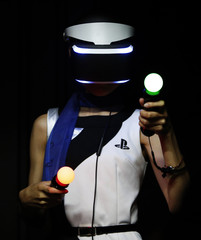 A staff of Sony Computer Entertainment tries out Play Station 4's virtual reality headset Project Morpheus at its booth in Tokyo Game Show 2014 in Makuhari, east of Tokyo