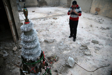 Akram Abu al-Foz takes a picture of a Christmas tree he decorated from empty shells which he collected and painted on, in the rebel held besieged city of Douma