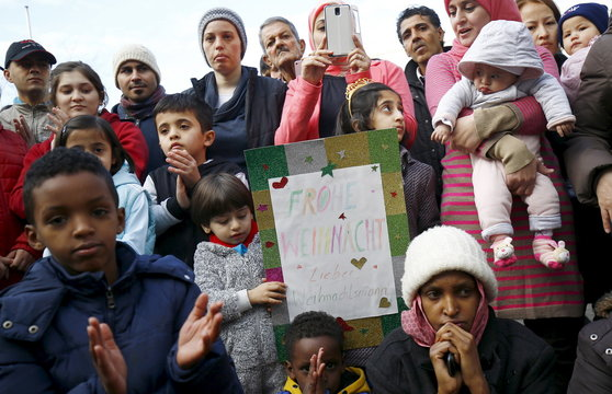 "Migrants hold a sign reading ""Merry Chrismas dear Father Christmas"" during a Christmas gathering organized by local relief organization "" Die Johanniter "" with christmas presents for the children at the refugee camp in Hanau, Germany"