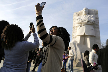 Catherine Abodo takes a picture of herself during a visit the Martin Luther King Jr. Memorial on the U.S. national holiday in his honor, in Washington