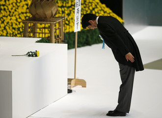 Japan's PM Abe bows after offering a flower during a memorial service for those who died in World War Two, in Tokyo