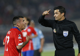 Chile's Medel talks to referee Ricci during the quarter-finals Copa America 2015 soccer match against Uruguay at the National Stadium in Santiago