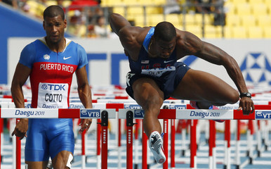 Oliver clears a hurdle next to Cotto during their men's 110 metres hurdles heats at the IAAF World Championships in Daegu