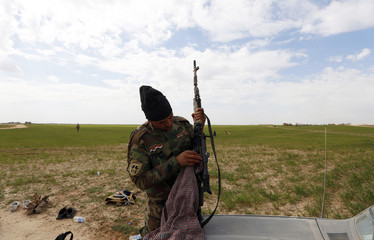 A Shi'ite fighter cleans his weapon in the town of Hamrin in Salahuddin province