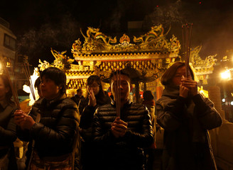 People pray with incense sticks at a temple as they celebrate the Lunar New Year in China Town, in Yokohama