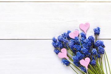Bouquet of blue muscaries flowers with decorative hearts on white wooden background. Place for text. Top view.