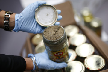 A member of the German Criminal Investigation Division displays a glass jar of seized heroin in Wiesbaden
