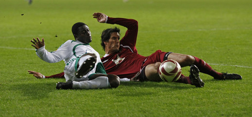 Wolfsburg's Martins tackles Rubin Kazan's Kabze during their Europa League last 16 second leg soccer match in Wolfsburg