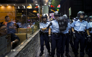 Riot police walk past a restaurant during a confrontation at Mongkok shopping district in Hong Kong