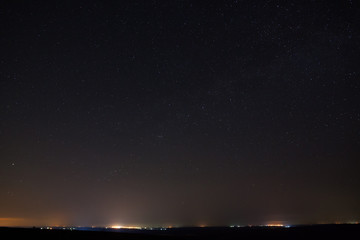 Stars in the dark night sky with city lights on the horizon.