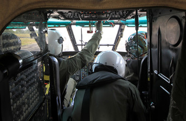 Indonesian Air Force pilots are seen in the cockpit of a Super Puma NAS 332 helicopter during a search and rescue operation over Kumai Bay