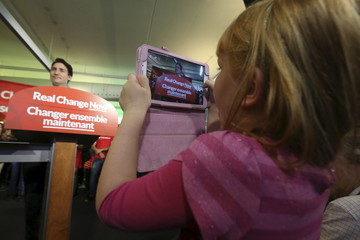 A girl takes a photo of Liberal leader Trudeau during a campaign stop in Hamilton