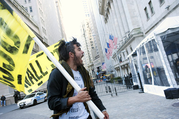 A member of the Occupy Wall Street movement chants along Wall Street after spending the night sleeping across the street from the New York Stock Exchange in New York