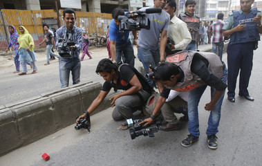 Members of media take pictures of abandoned homemade hand bomb after alleged activists of Bangladesh Nationalist Party threw it at police in Dhaka
