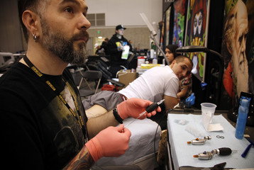 Artist Sean Karn prepares his needle before applying a tattoo of Captain America on the leg of Ron Raucci during the Hampton Roads Tattoo Festival in Virginia
