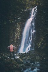 Hiker standing in front of the waterfall. Instagram stylization