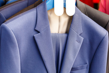 A man's jacket hangs on a hanger in a clothing store
