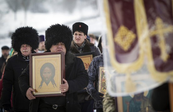Orthodox believers carry icons as they walk in procession during Epiphany celebration in Almaty