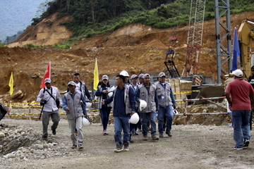 Chinese and Ecuadorean workers walk by during a ceremony marking the start of construction of a mine owned by Chinese mining company EcuaCorriente in el Pangui