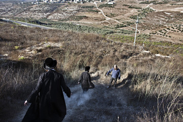 Netanel, an Israeli Jewish settler, waits as two friends come to visit him in a field at the unauthorised Jewish settler outpost of Havat Gilad, south of Nablus