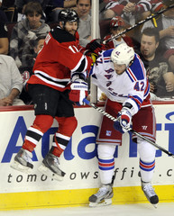 New York Rangers' Artem Anisimov checks New Jersey Devils' Stephen Gionta during the third period in game 3 of their NHL Eastern Conference Final hockey playoff game in Newark