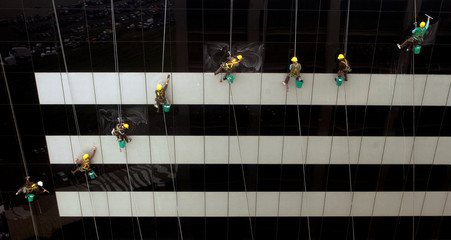 Workers clean windows at a building in downtown Buenos Aires