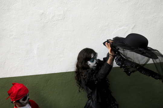 "A girl with her face painted to look like the popular Mexican figure called ""Catrina"", tries to put on her hat as she takes part in the annual Catrina Fest in Mexico City"