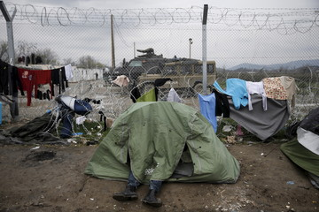 A migrant sits inside a tent next to the border fence at the Greek-Macedonian border, at a makeshift camp for refugees and migrants near the village of Idomeni