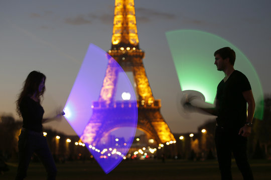 Marion and Nikola, members of the Sport Saber League, pose with their light sabers in front of the Eiffel tower in Paris, France