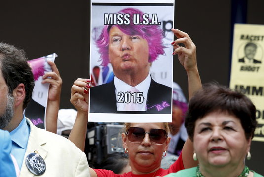 A woman raises a picture during a protest calling for businesses to sever their relationships with U.S. Republican presidential candidate Donald Trump