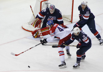 Hertl of Czech Republic battles for puck with Stapleton of the U.S. in men's ice hockey World Championship quarter-final game in Minsk