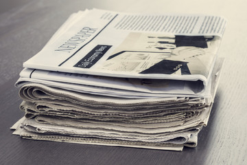 Stack of newspaper on wooden table