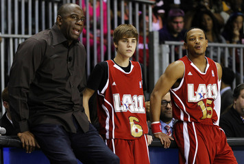 Recording artist Bieber stands with NBA basketball hall of famer Johnson and rapper Miller during 2011 BBVA All-Star Celebrity basketball game as a part of the NBA All-Star basketball weekend in Los Angeles