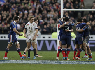 France players celebrate after defeating England in  their Six Nations rugby union match at the Stade de France in Saint-Denis