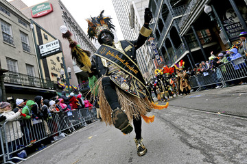 A member of the Zulu Social Aid and Pleasure Club parades down St. Charles Avenue on Mardi Gras in New Orleans, Louisiana