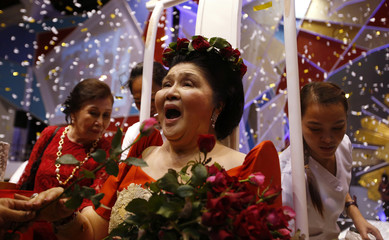 Former Philippine first lady and congresswoman Imelda Marcos receives flowers from supporters during her 85th birthday celebration, in Laoag, Ilocos Norte